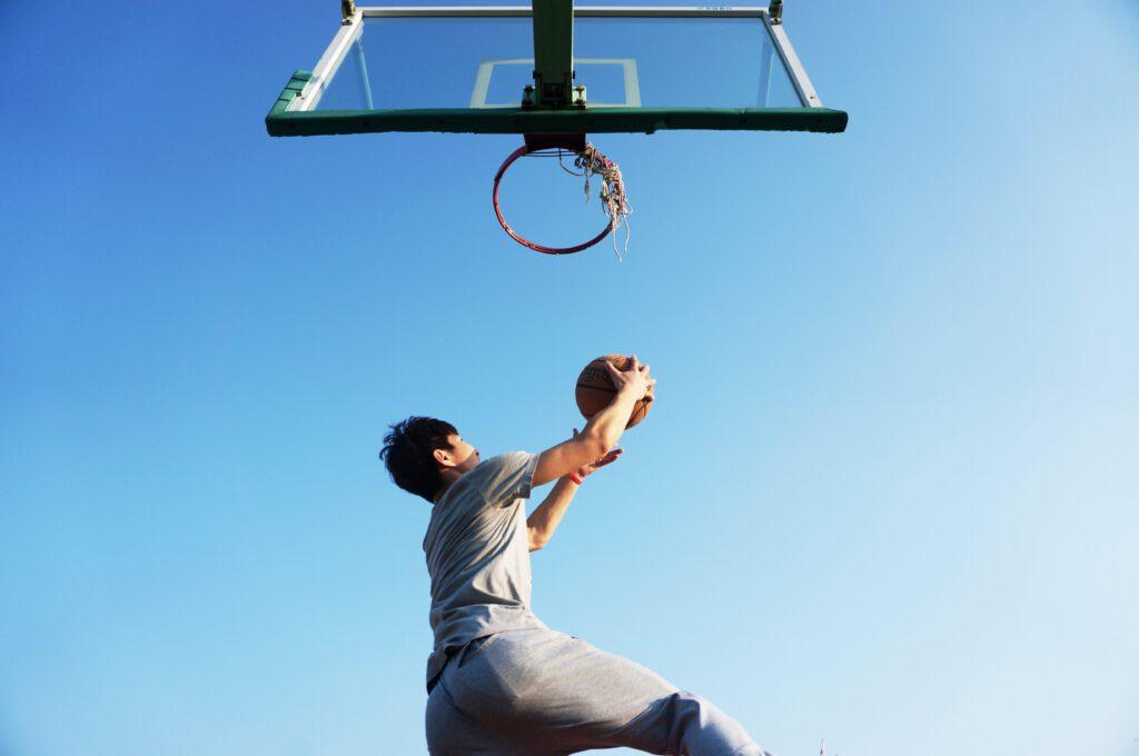 Basketballer taucht mit Ball unter dem Korb durch