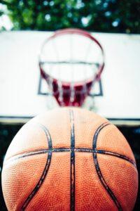Ein Basketball liegt am Boden vor einem Korb, der im Hintergrund leicht verschwommen zu sehen ist.
