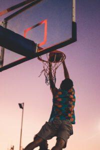 Basketballspieler dunkt auf Freiplatz bei Sonnenuntergang