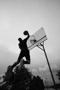 Spieler fliegt mit Ball auf Freiplatz zum Korb